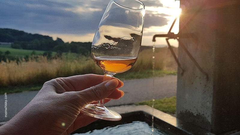 Die untergehende Sonne spiegelt sich im Whiskyglas